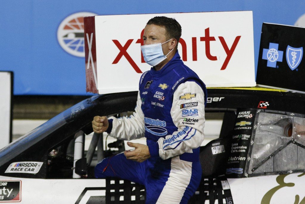 AJ Allmendinger climbs out of his car in Victory Lane after winning a NASCAR Xfinity Series auto race at Charlotte Motor Speedway in Concord, N.C., Sa...