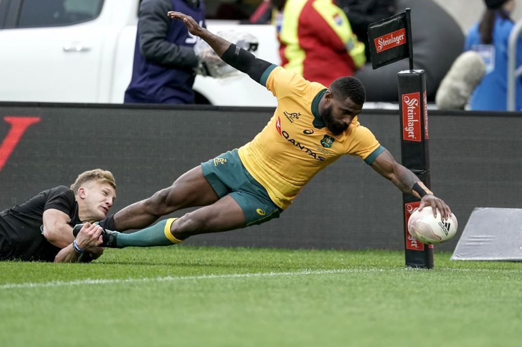 Australia's Marika Koroibete, right, scores a try in the tackle of New Zealand's Damian McKenzie during the Bledisloe Cup rugby game between the All B...