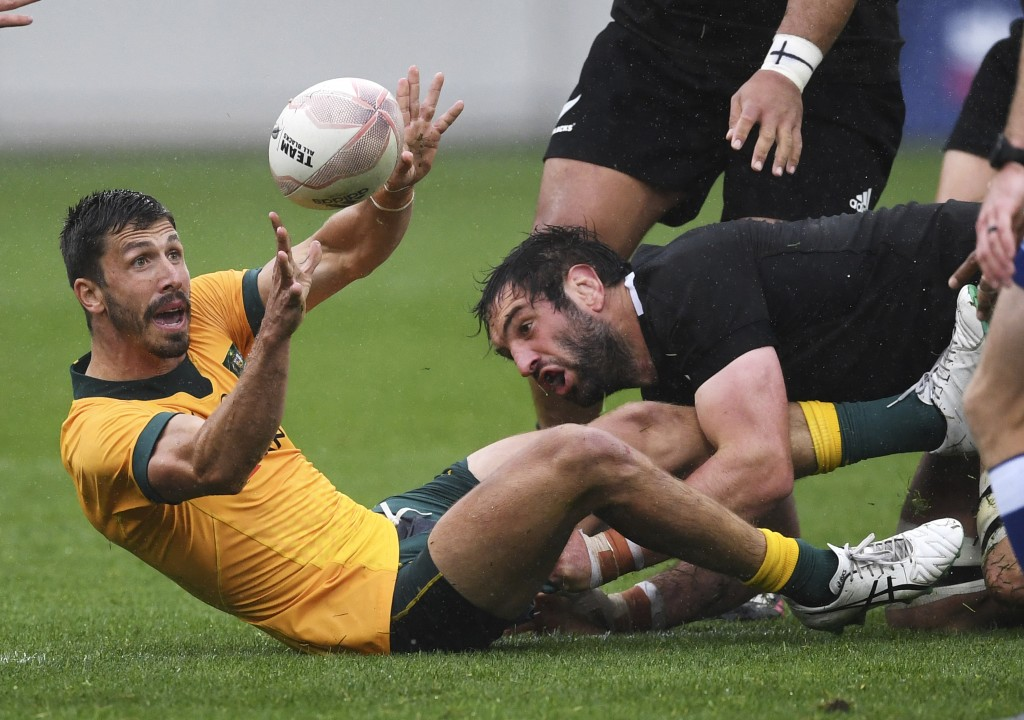 Australia's Jake Gordon passes the ball in the tackle of New Zealand's Sam Whitelock during the Bledisloe Cup rugby game between the All Blacks and th...