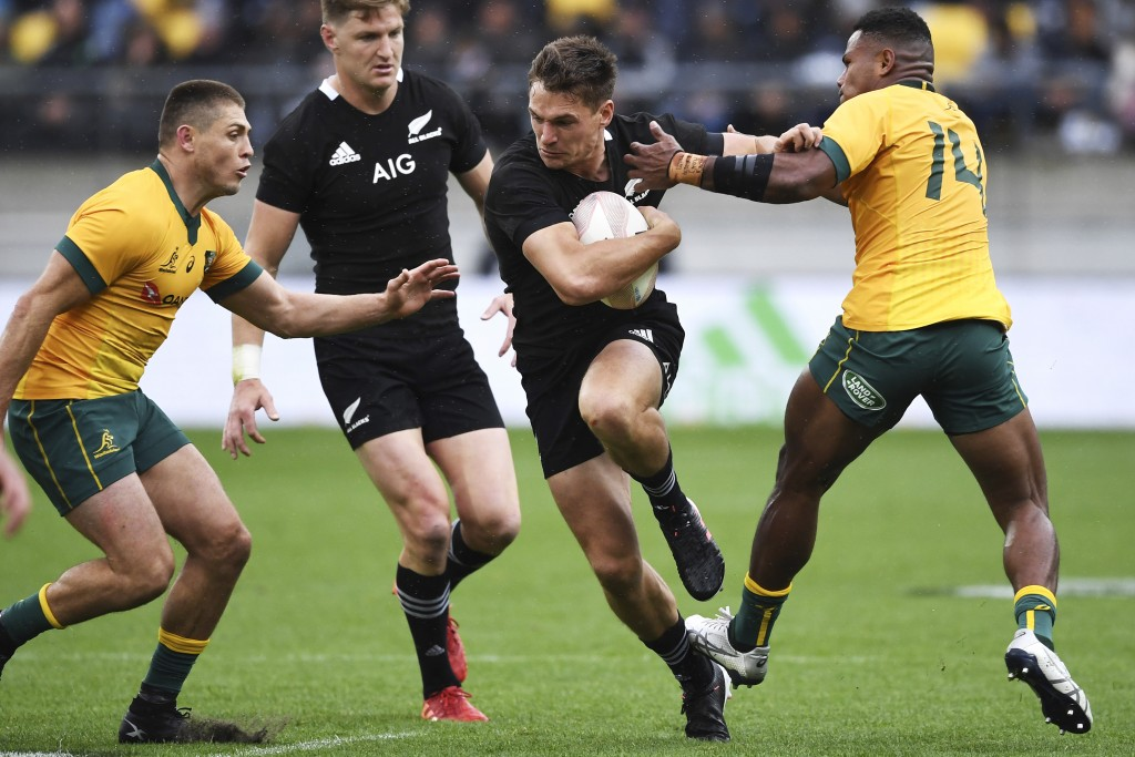New Zealand's George Bridge runs between Australia's Filipo Daugunu, right, and James O'Connor, left, during the Bledisloe Cup rugby game between the ...