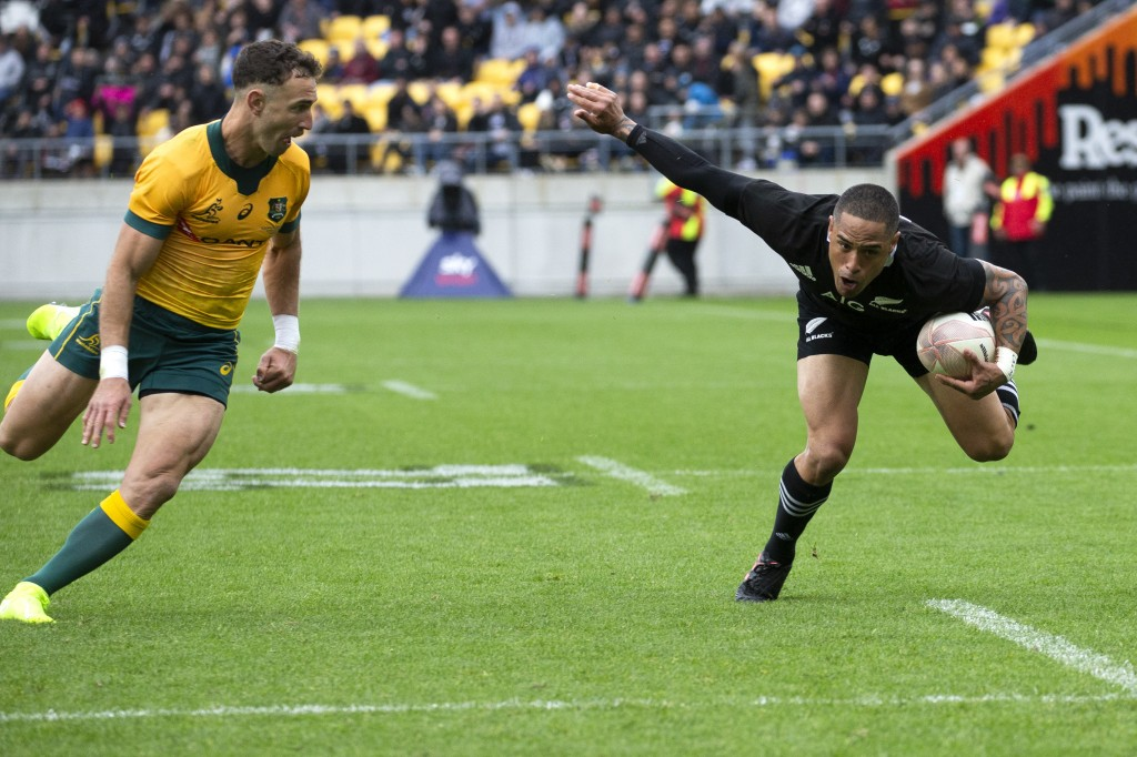 New Zealand's Aaron Smith runs to score a try as Australia's Nic White, left, comes in for the tackle during the Bledisloe Cup rugby game between the ...