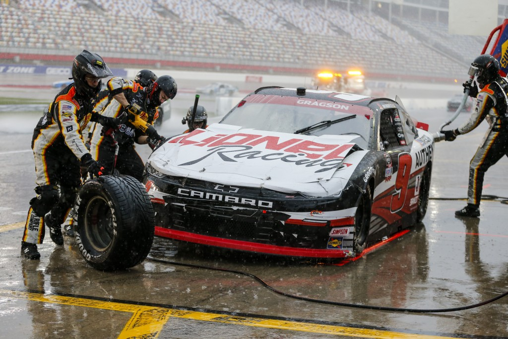 Noah Gragson's pit crew work on his damaged car during a yellow flag pit stop during a NASCAR Xfinity Series auto race at Charlotte Motor Speedway in ...