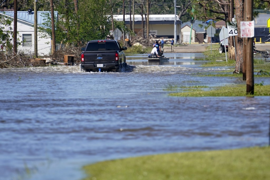A truck drive through floodwaters in a neighborhood in Lake Charles, La., Saturday, Oct. 10, 2020, after Hurricane Delta moved through on Friday. (AP ...