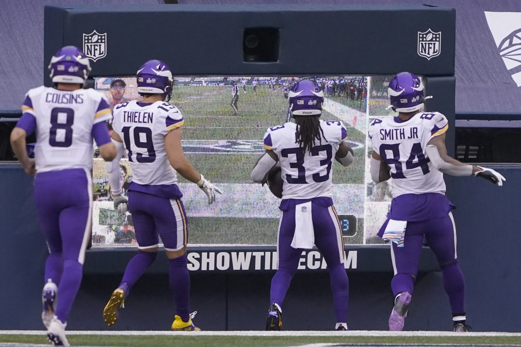 Minnesota Vikings' Dalvin Cook (33) heads to a monitor with teammates to celebrate after scoring against the Seattle Seahawks during the first half of...