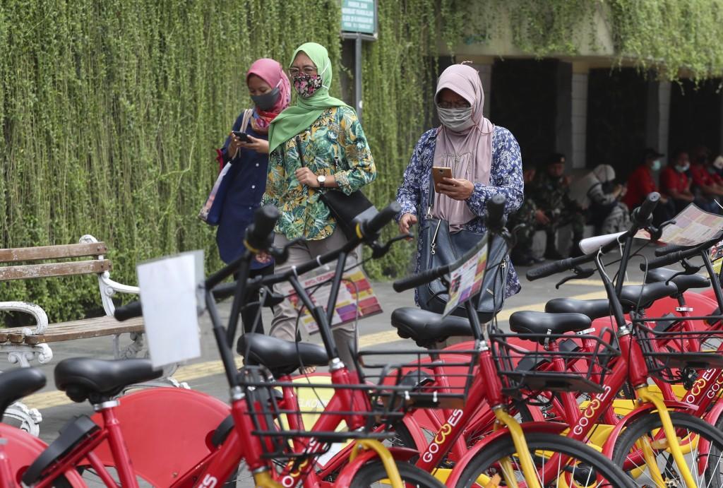 Indonesian women wearing masks as a precaution against the coronavirus outbreak walk on a pedestrian street in Jakarta Monday, Oct. 12, 2020.(AP Photo...