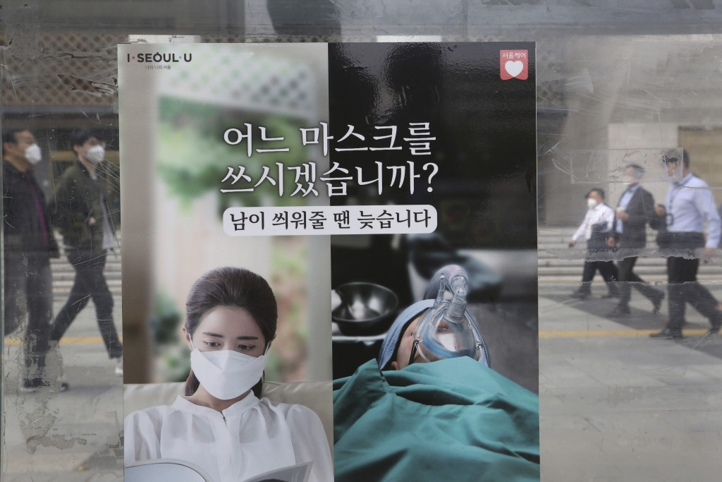 People wearing face masks to help protect against the spread of the coronavirus walk by a poster informing mandatory mask wearing, at a bus station in...