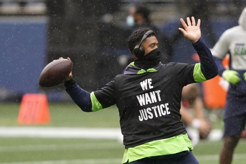Seattle Seahawks quarterback Russell Wilson warms-up in a light rain before an NFL football game against the Minnesota Vikings, Sunday, Oct. 11, 2020,...