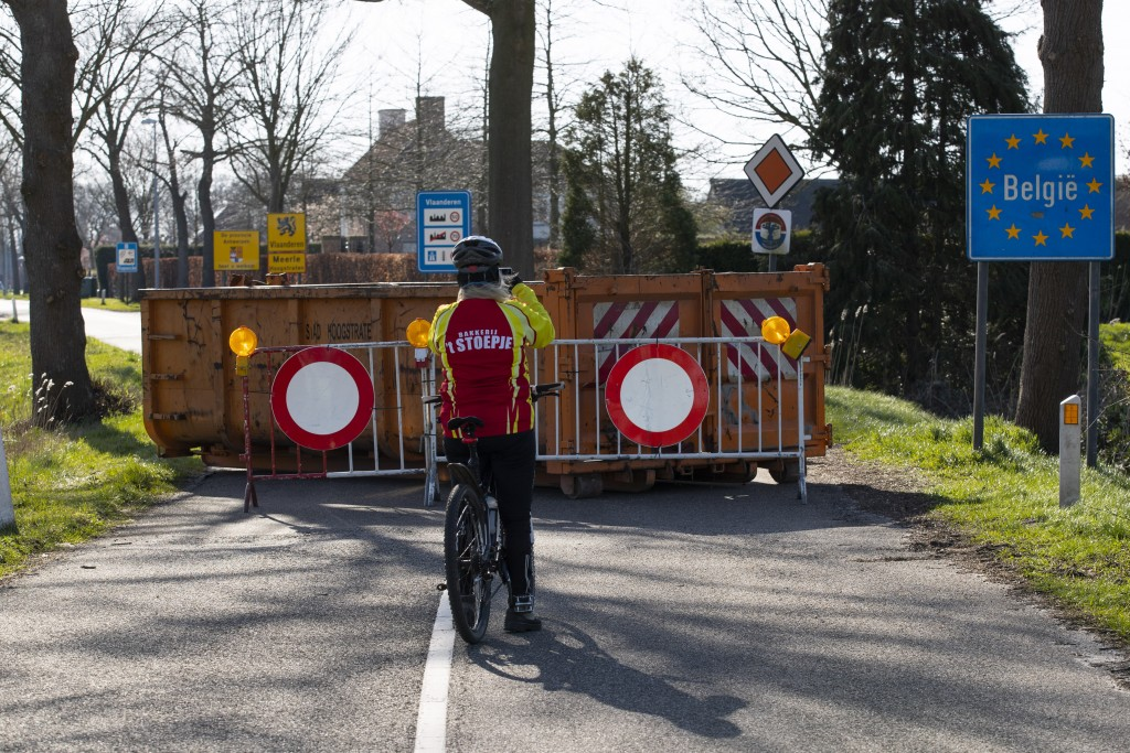 FILE - In this Monday, March 23, 2020 file photo, a cyclist takes images of a barricaded backroad used by locals on the Netherlands border with Belgiu...