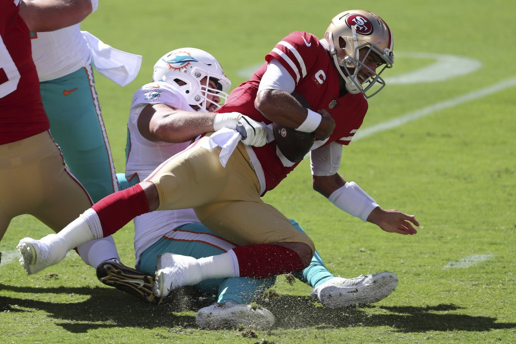 Miami Dolphins defensive end Zach Sieler, left, sacks San Francisco 49ers quarterback Jimmy Garoppolo during the first half of an NFL football game in...