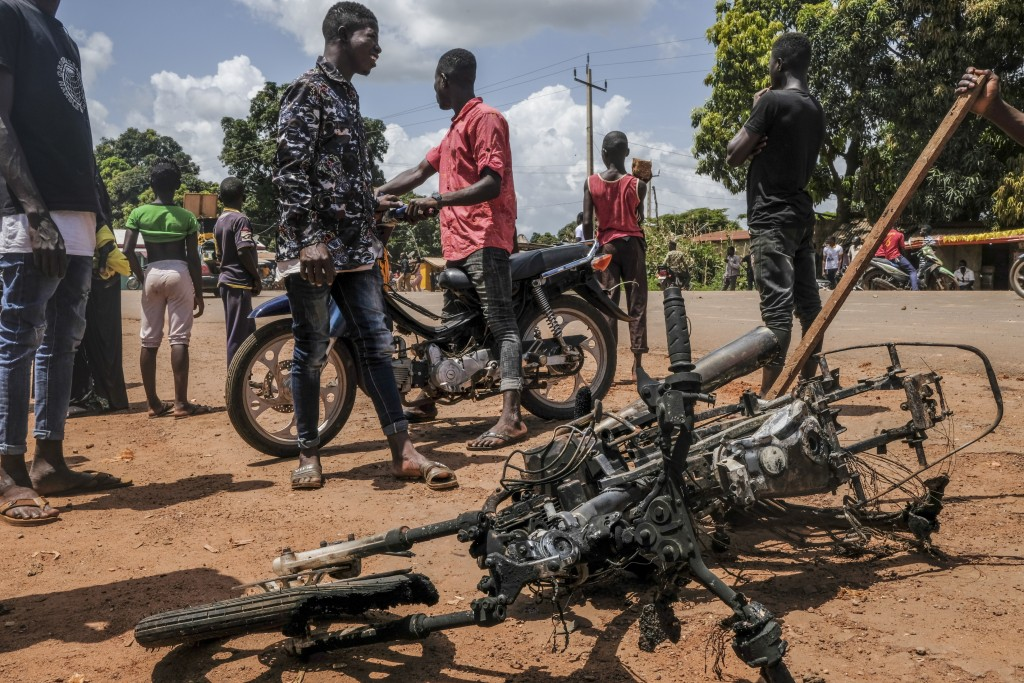 The burned motorcycle of an opposition activist, who was lightly injured and fled, lies on the ground as supporters of the ruling Rally of the Guinean...