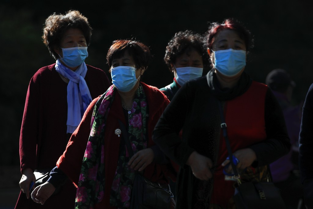 Women wearing face masks to help curb the spread of the coronavirus walk across a street in Beijing, Monday, Oct. 12, 2020. Even as China has largely ...