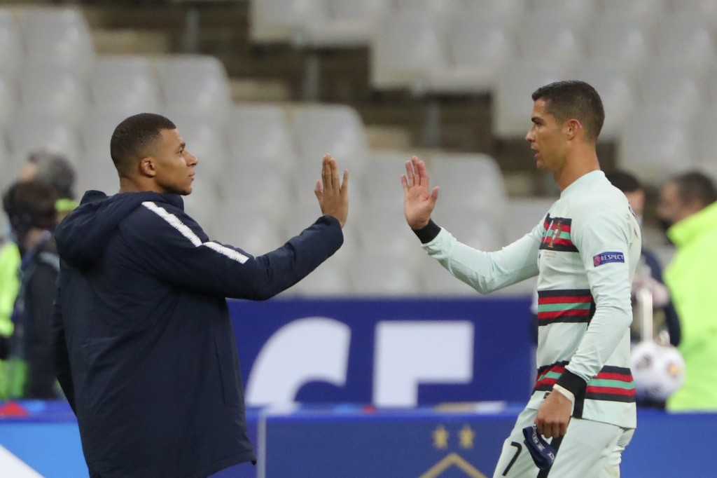 France's Kylian Mbappe and Portugal's Cristiano Ronaldo, right, greet each other at the end of the UEFA Nations League soccer match between France and...