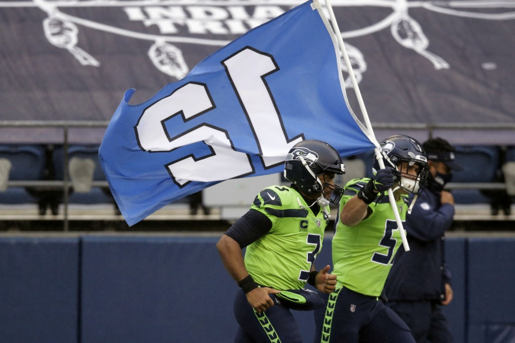 Seattle Seahawks' Cody Barton carries the 12th flag onto the field as he runs with quarterback Russell Wilson before an NFL football game against the ...