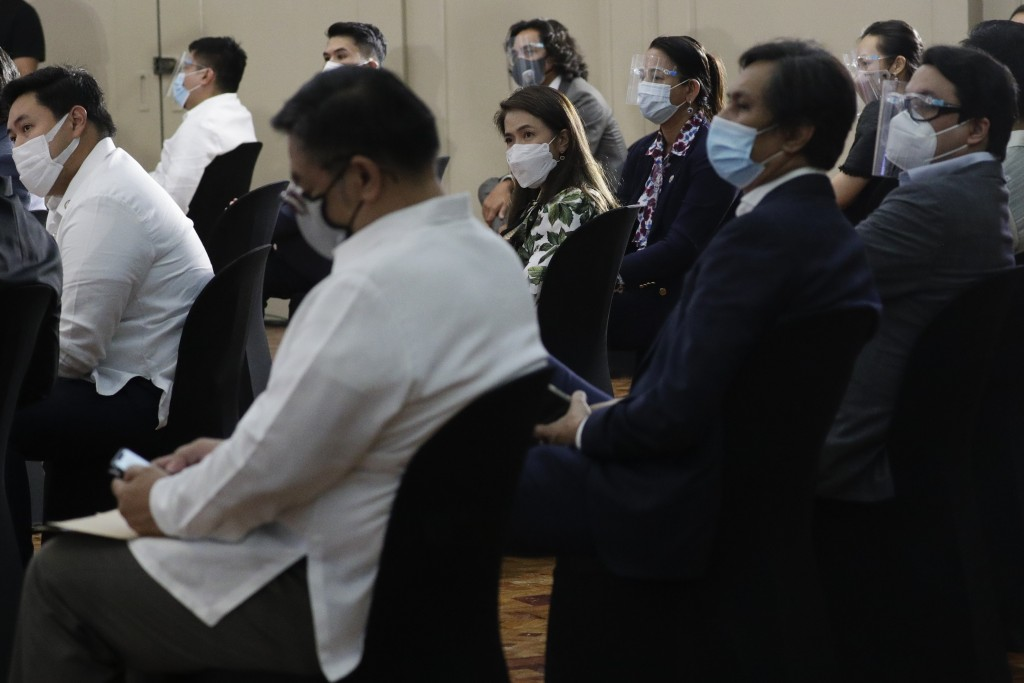 Filipino lawmakers wear face masks as they attend a session before swearing in Rep. Lord Allan Velasco as new house speaker at the Celebrity sports cl...