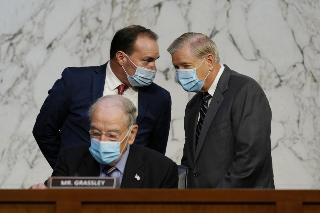 Senate Judiciary Committee Chairman Sen. Lindsey Graham, standing right, talks to Sen. Mike Lee, R-Utah., as Sen. Charles Grassley, R-Iowa, sits below...