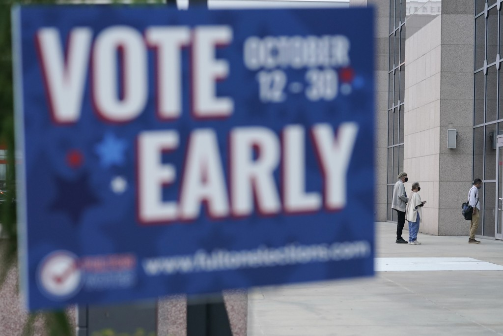 A line forms outside of the State Farm Arena for early voting on Monday, Oct. 12, 2020, in Atlanta. (AP Photo/Brynn Anderson)