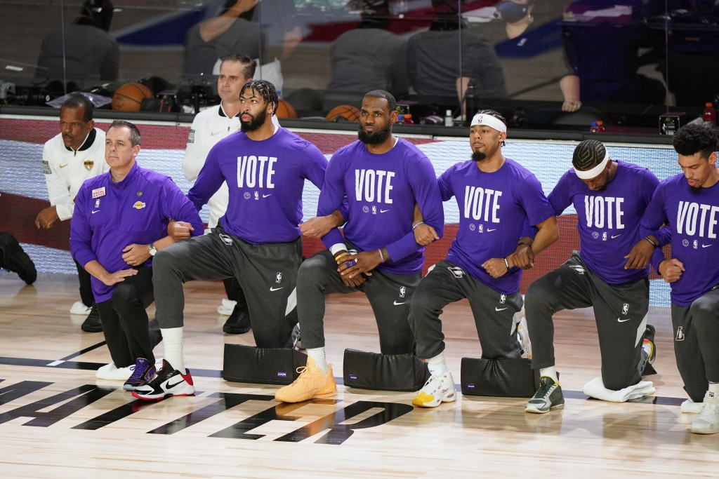 Members of the Los Angeles Lakers kneel as center Meyers Leonard stands before Game 6 of basketball's NBA Finals against the Miami Heat Sunday, Oct. 1...