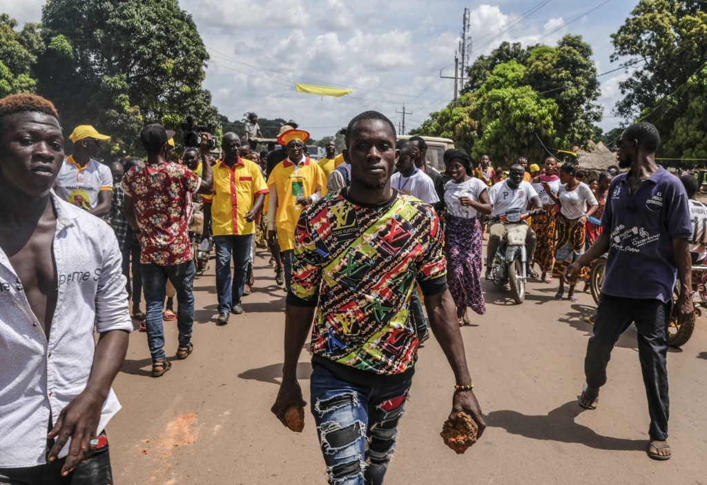 A supporter of the ruling Rally of the Guinean People (RPG) party holds rocks as he and others demonstrate against the opposition Union of Democratic ...