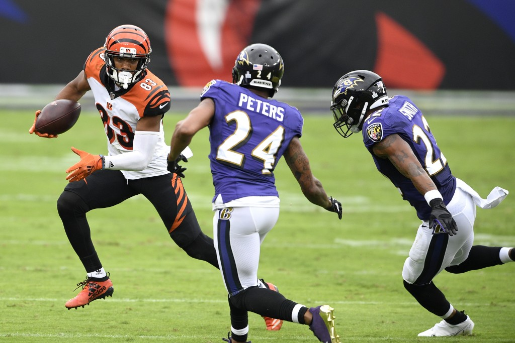 Cincinnati Bengals wide receiver Tyler Boyd (83) runs with the ball as Baltimore Ravens cornerback Marcus Peters (24) and cornerback Jimmy Smith (22) ...