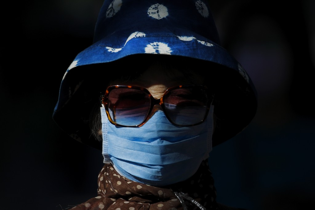 A beam of sunlight is cast on a woman wearing a face mask to help curb the spread of the coronavirus as she walks on a street in Beijing, Monday, Oct....