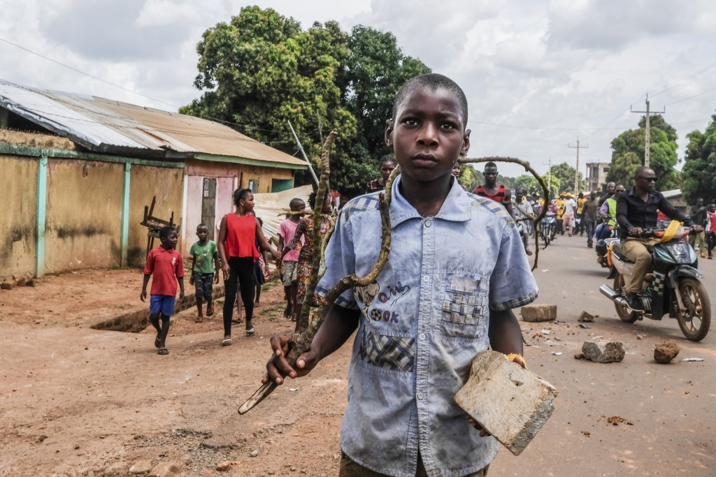 A child holds a stick and rock as supporters of the ruling Rally of the Guinean People (RPG) party demonstrate against the opposition Union of Democra...
