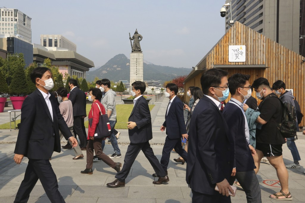 People wearing face masks to help protect against the spread of the coronavirus cross a road in Seoul, South Korea, Monday, Oct. 12, 2020. (AP Photo/A...