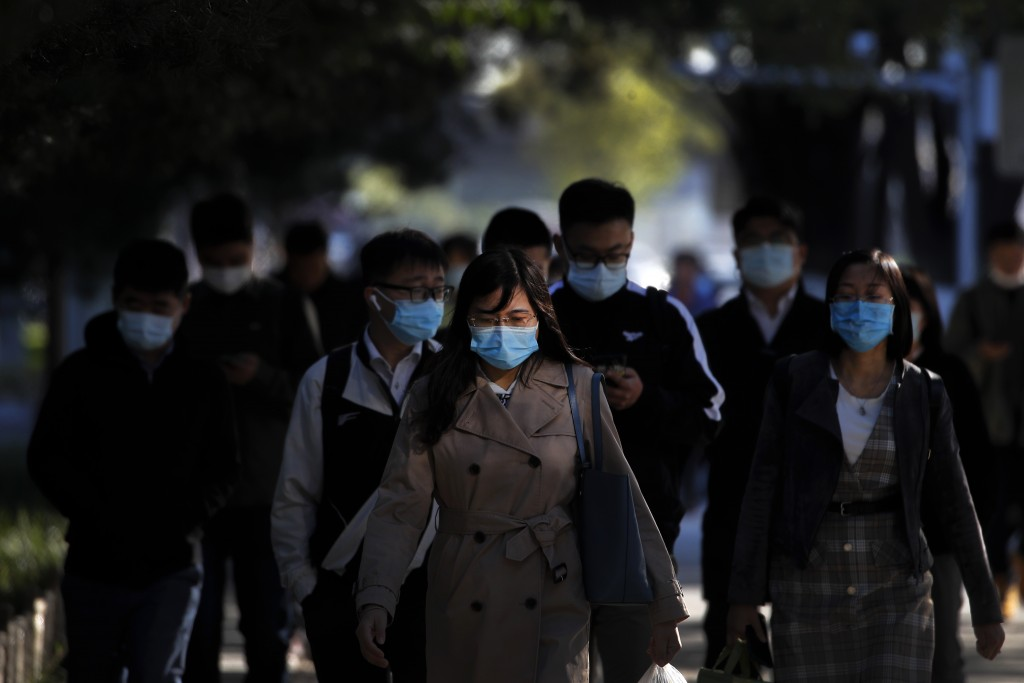 People wearing face masks to help curb the spread of the coronavirus walk on a street during the morning rush hour in Beijing, Monday, Oct. 12, 2020. ...