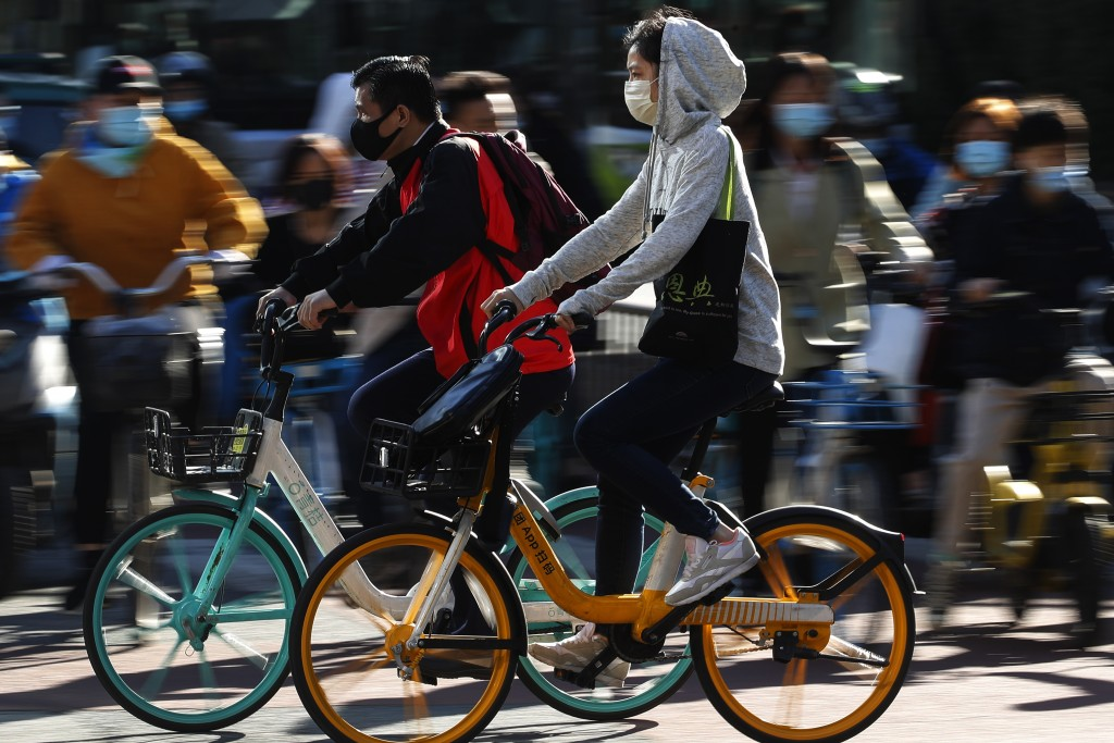 People wearing face masks to help curb the spread of the coronavirus ride bicycle during the morning rush hour in Beijing, Monday, Oct. 12, 2020. Even...