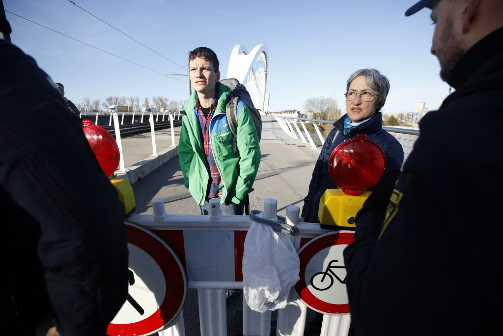 FILE - In this March 16, 2020 file photo, German police officers prevent people from entering Germany at the German-France border in Kehl, Germany. Eu...