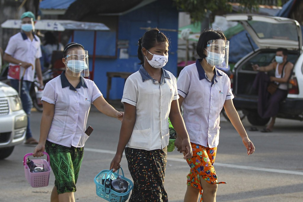 Factory workers wearing protective face masks and shields cross a road as they go to work in Hlaing Tharyar Industrial Zone Monday, Oct. 12, 2020, on ...