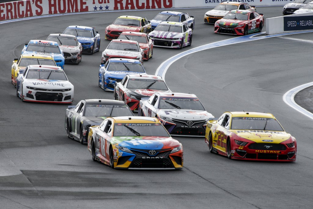 Kyle Busch (18) and Joey Logano (22) lead the pack out of Turn 2 in a NASCAR Cup Series auto race at Charlotte Motor Speedway in Concord, N.C., Sunday...