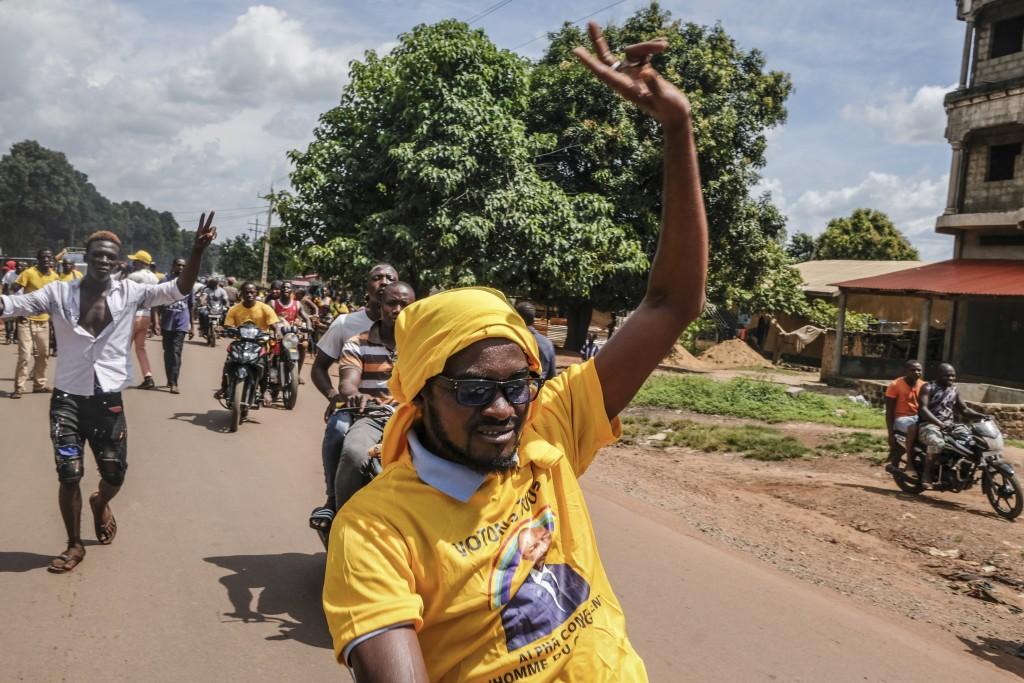 Supporters of the ruling Rally of the Guinean People (RPG) party, one wearing a t-shirt of the president, ride on motorbikes at a demonstration agains...