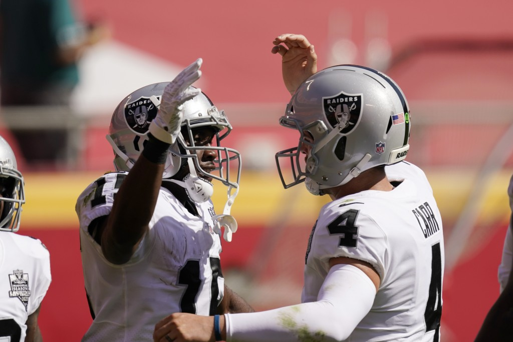 Las Vegas Raiders wide receiver Nelson Agholor, left, celebrates with quarterback Derek Carr after catching a 59-yard touchdown pass during the first ...