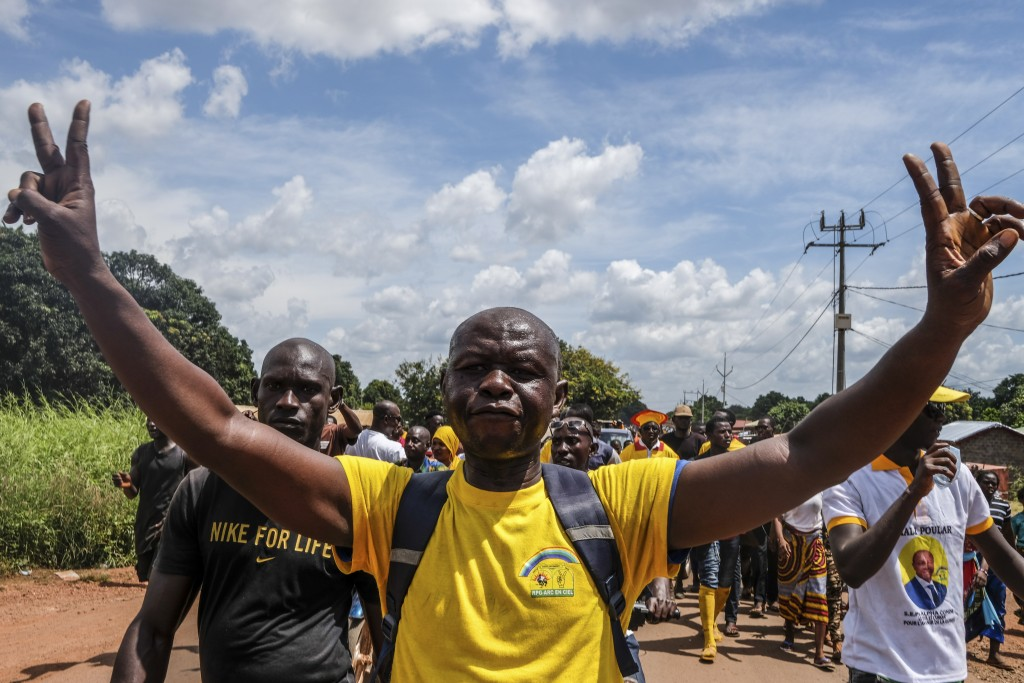 A supporter of the ruling Rally of the Guinean People (RPG) party joins others to demonstrate against the opposition Union of Democratic Forces of Gui...