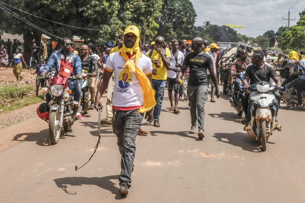 Supporters of the ruling Rally of the Guinean People (RPG) party, one wearing a t-shirt of the president and holding a rubber whip, demonstrate agains...