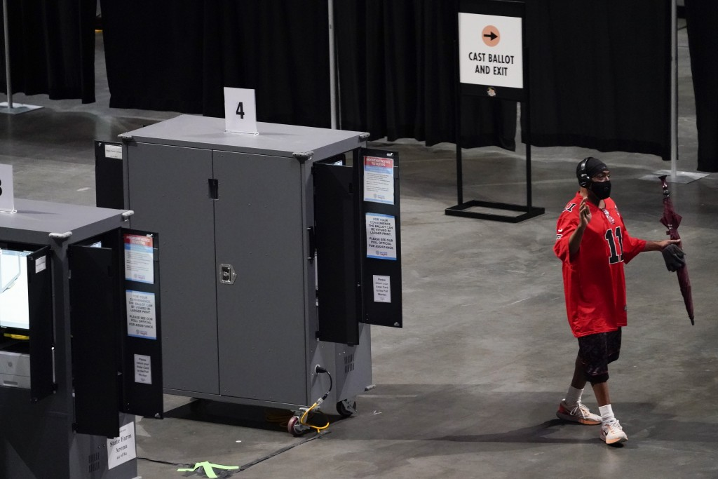 A man tries to vote but walks away after the machine stopped working during early voting at the State Farm Arena on Monday, Oct. 12, 2020, in Atlanta....