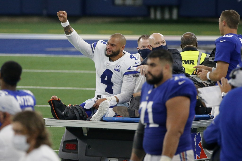 Dallas Cowboys quarterback Dak Prescott (4) lifts his fist to cheers from fans as he is carted off the field after suffering a lower right leg injury ...