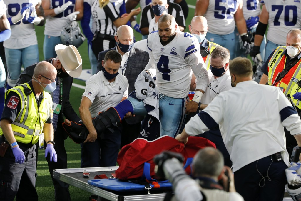 Dallas Cowboys quarterback Dak Prescott (4) is assisted by first responders and team medical staff onto a cart after suffering a leg injury running th...