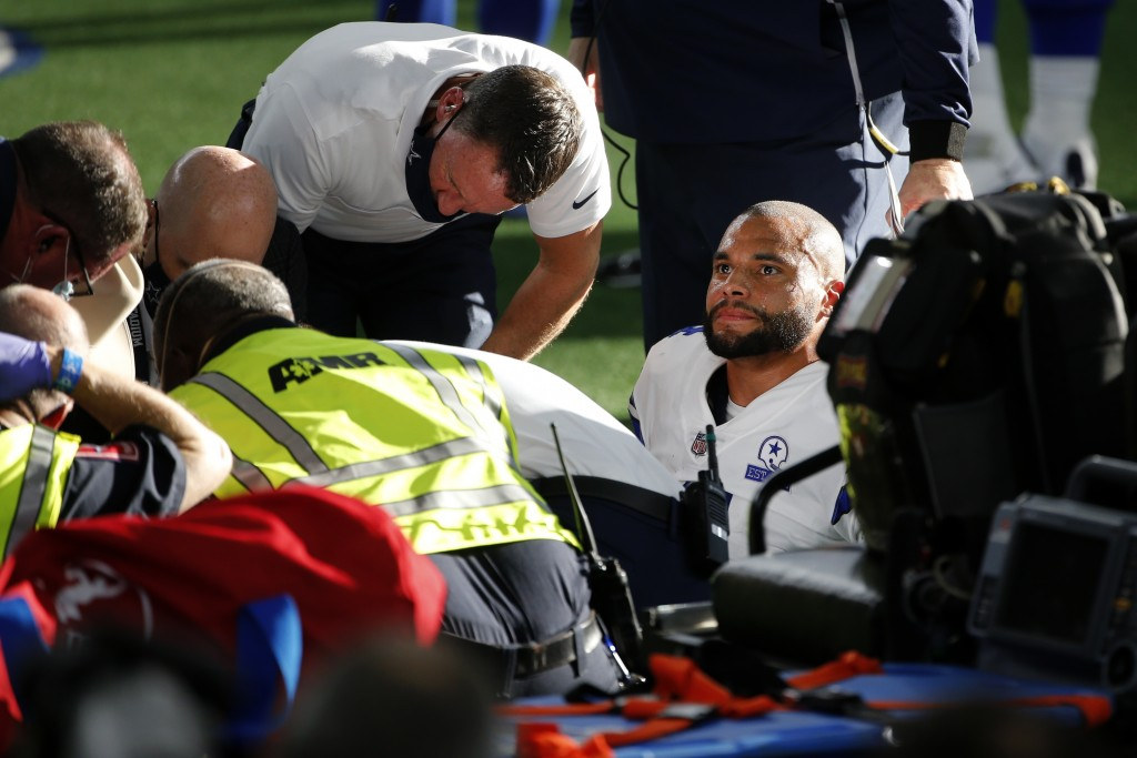 Dallas Cowboys quarterback Dak Prescott, right, looks off as first responders and team medical personnel assist Prescott after he suffered a lower rig...