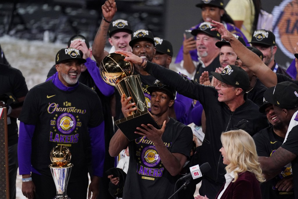 Los Angeles Lakers' Rajon Rondo (9) holds the trophy as he celebrates with his teammates after the Lakers defeated the Miami Heat 106-93 in Game 6 of ...