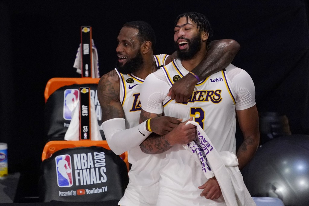 Los Angeles Lakers' LeBron James (23) and Anthony Davis (3) celebrate after the Lakers defeated the Miami Heat 106-93 in Game 6 of basketball's NBA Fi...