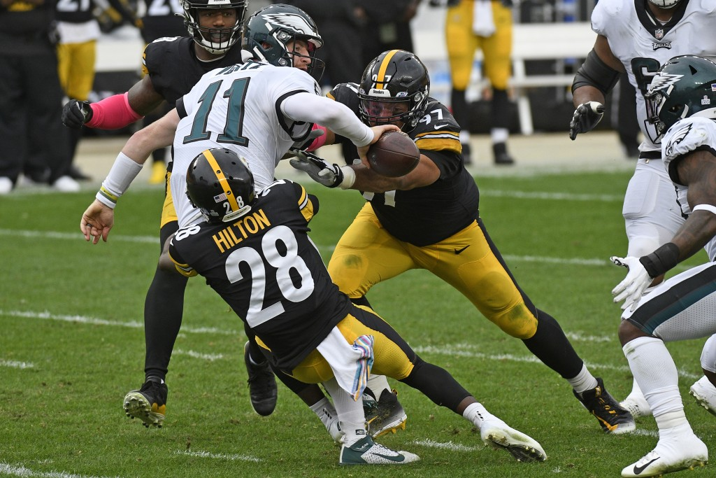 Philadelphia Eagles quarterback Carson Wentz (11) is sacked by Pittsburgh Steelers cornerback Mike Hilton (28) and Cameron Heyward (97) during the sec...