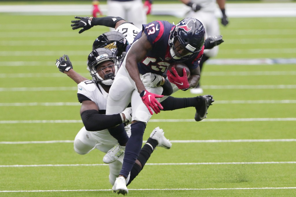 Houston Texans wide receiver Brandin Cooks (13) is hit by Jacksonville Jaguars safety Daniel Thomas (20) after a catch during the second half of an NF...