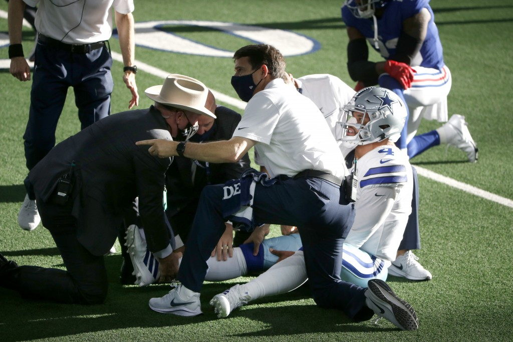 Dallas Cowboys quarterback Dak Prescott, right, is receives medical assistance from first responders and team medical personnel after Prescott suffere...