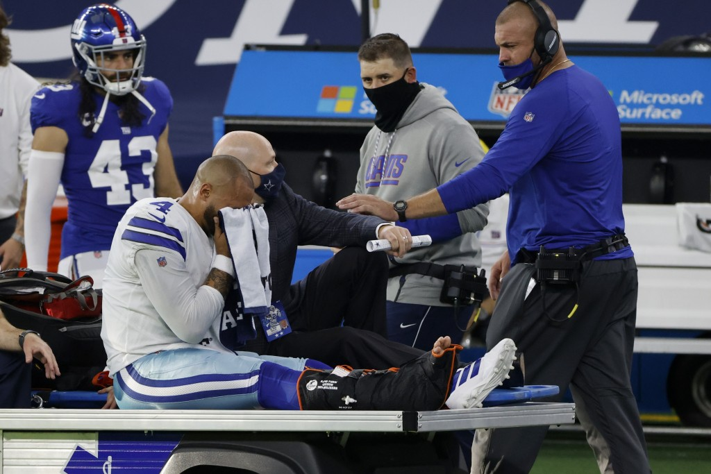 An emotional Dallas Cowboys quarterback Dak Prescott, wipes his face with a towel as he is carted off the field after suffering an unknown right lower...