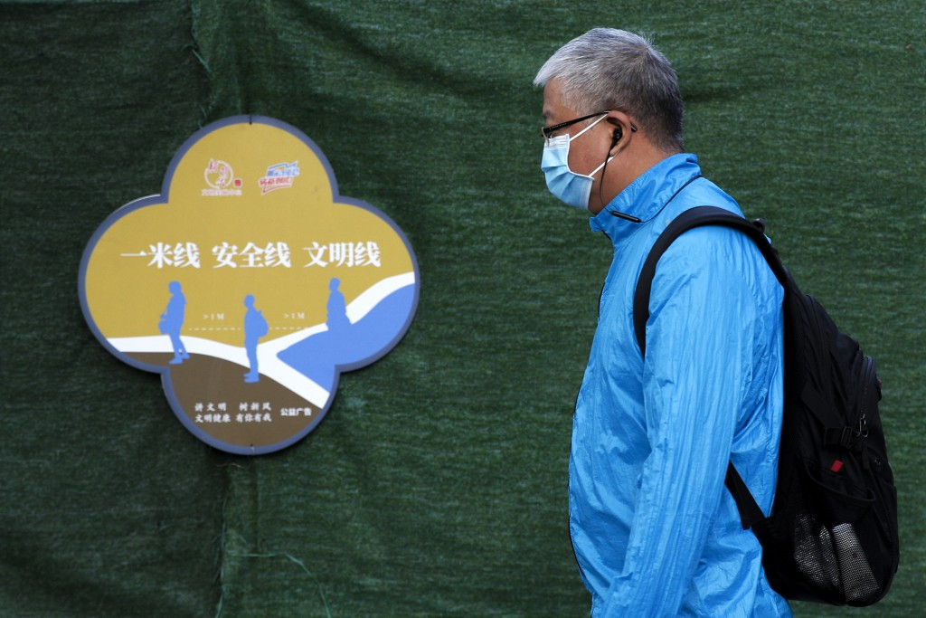 A man wearing a face mask to help curb the spread of the coronavirus walks by a poster which advises people for social distancing, on a street in Beij...