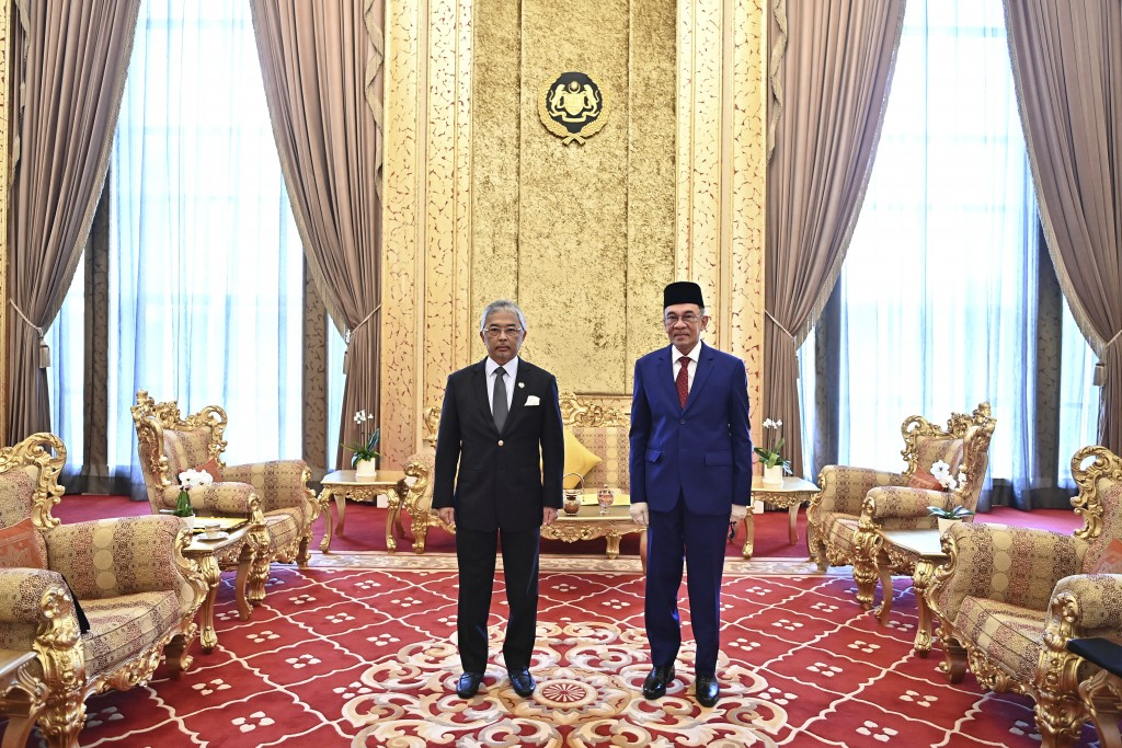 In this handout photo provided by the Malaysian National Palace, The King of Malaysia, Sultan Abdullah Sultan Ahmad Shah, left, and opposition leader ...
