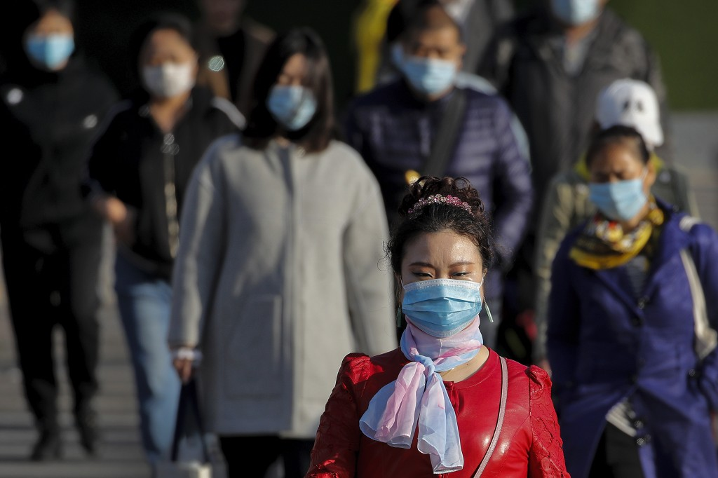 People wearing face masks to help curb the spread of the coronavirus walk across a street during the morning rush hour in Beijing, Tuesday, Oct. 13, 2...