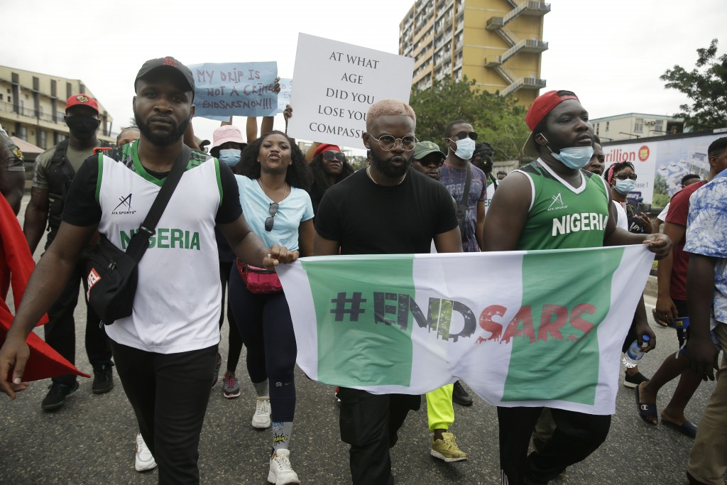 People hold banners as they demonstrate on the street to protest against police brutality in Lagos, Nigeria, Tuesday Oct. 13, 2020. Crowds protesting ...