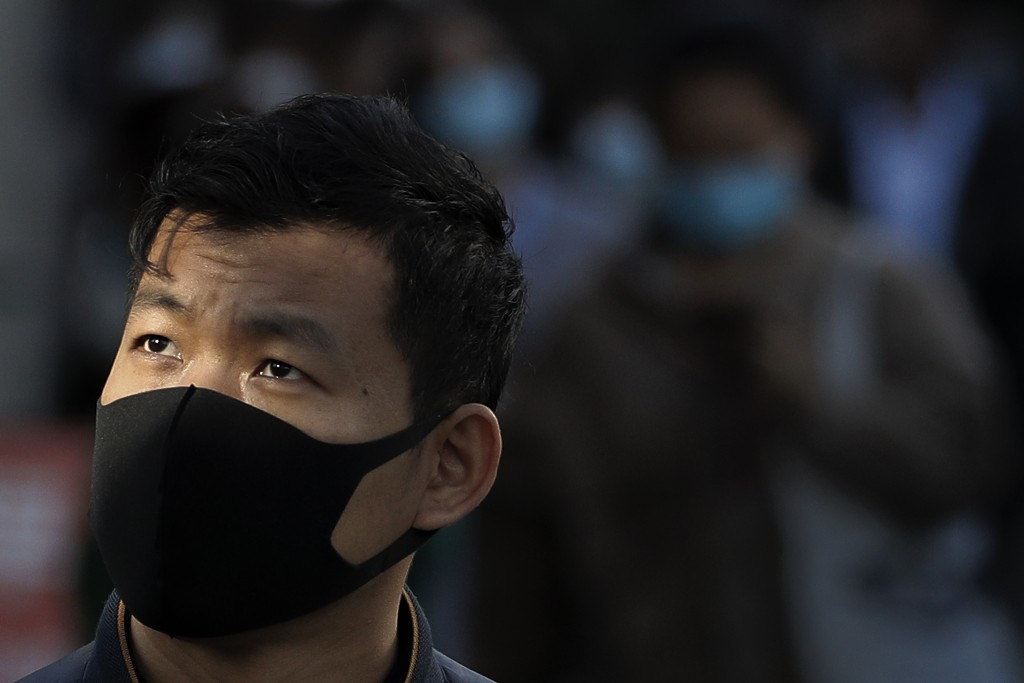 A man wearing a face mask to help curb the spread of the coronavirus walks along a street with masked people in Beijing, Tuesday, Oct. 13, 2020. (AP P...